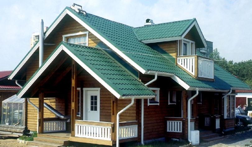 Зеленая металлочерепица на крыше с белой подшивкой на доме из бруса