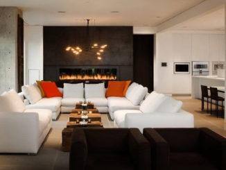 Ярко-оранжевые подушки создают акценты на белоснежном диване