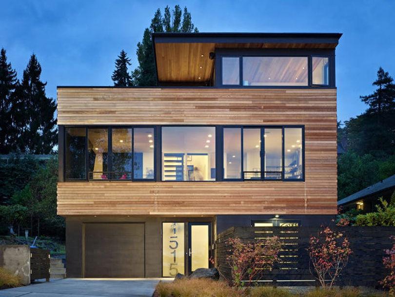 Трехэтажный дом с плоской крышей с фасадом под дерево