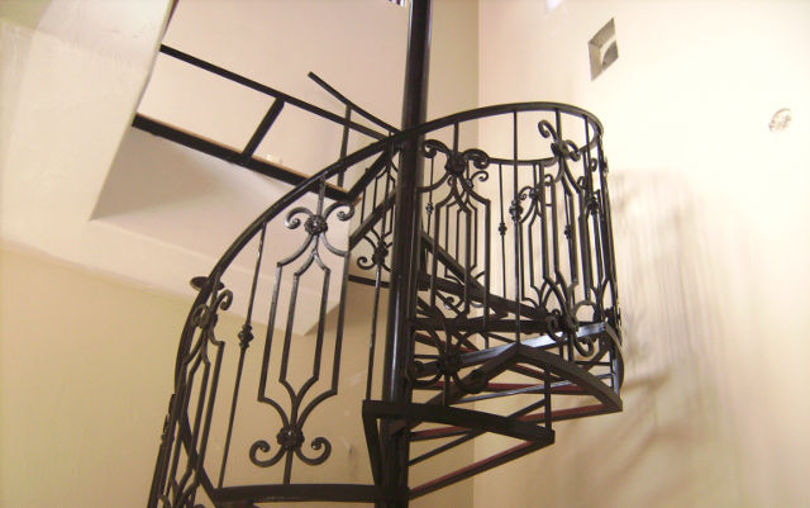 Винтовая лестница с металлически каркасом и кованными перилами